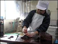 A woman in  Mr Shoji's factory cutting whale meat