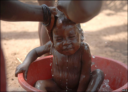 A baby being washed in a bowl in a displacement camp in northern Uganda