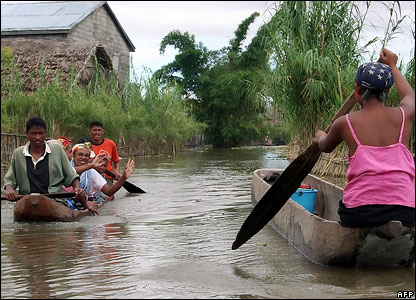 Madagascans paddle through a village