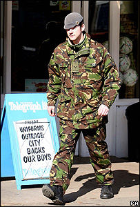 A soldier from RAF Wittering walks past a billboard in Wittering Village, Cambridgeshire.