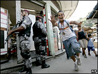 A boy runs past police officers guarding the streets of the Complexo de Alemao slum in Rio de Janeiro, 6 March 2008