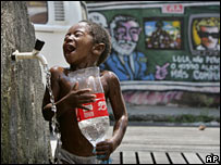 A boy washes at a public tap in the Complexo de Alemao slum in Rio de Janeiro, Thursday, March 6, 2008.