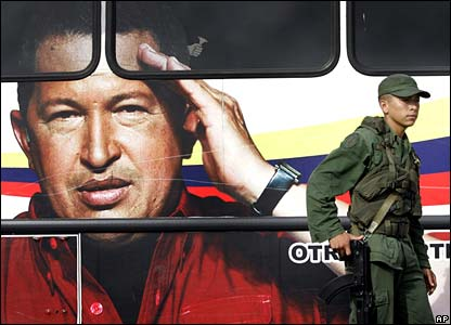 A Venezuelan soldier stands in front of a bus decorated with a photograph of President Chavez at a checkpoint in Paraguaipoa, on the border with Colombia, on Thursday