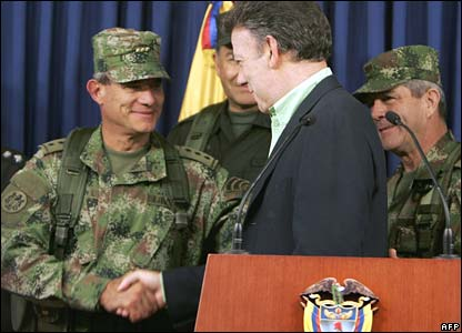 Colombian Defence Minister Juan Manuel Santos (C) shakes hands with the Armed Forces General Commandant, General Freddy Padilla, at the news conference at which Reyes's death was announced