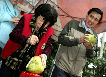 Ma Ying-jeou, presidential candidate of Taiwan's opposition Nationalist Party, receives a coconut from Chen Tao, a former comfort woman who was allegedly forced into prostitution and sexual slavery by