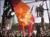 Afghan protesters burn the flags of Denmark and German during a demonstration in Herat