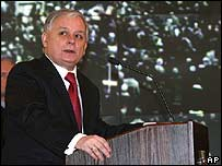 Lech Kaczynski standing in front of an archive 1968 photo of the riots at the anniversary ceremony