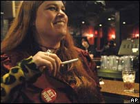 "Courtney Conk wears an ""Act Now"" badge as she smokes in a bar in Minnesota"