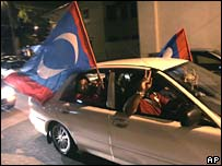 Supporters of Malaysia's opposition Justice Party celebrate election results early on Sunday in Kuala Lumpur