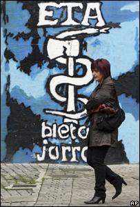 Mujer pasa delante de mural en calle española