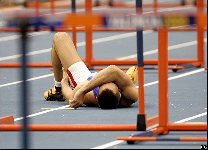 Roman Sebrle writhes on the ground during the 60m hurdles