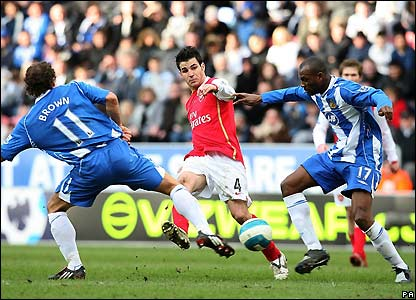 Fabregas looks to thread a ball through Wigan's midfield