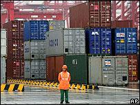Un trabajador chino está delante de los container de un puerto en Shangai.