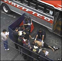 Investigators gather evidence at a crime scene after a bus driver was shot in the head in Guatemala City on 7 February 2008