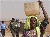 Woman walks past UN peacekeepers in Darfur refugee camp