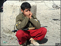 An Iraqi youth carrying an AK-47 machine gun weeps at the site of a suicide bombing Diyala province, Iraq, 10 March 2008