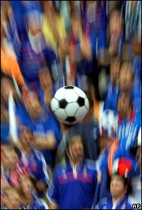 An inflatable football in the air with football fans in the background