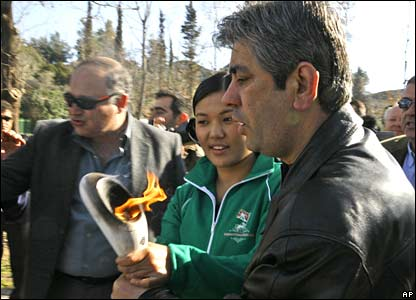 Greek plain clothes police offices try to take away the torch from the hands of Tsultim Gope, centre, a shot-putter and member of the Tibet team