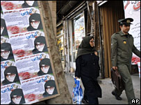 Iranians walk past campaign posters for parliamentary candidate Fatemeh Karroubi in Tehran, 10 March, 2008