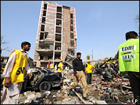 Pakistani rescue workers and police officials examine the bomb blast in front of badly damaged building of the Federal Investigation Agency in Lahore