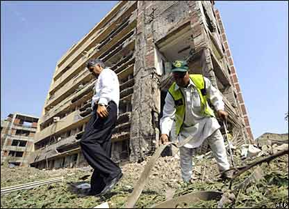 Pakistani investigators examine the bomb blast site in front of the badly damaged building of the Federal Investigation Agency