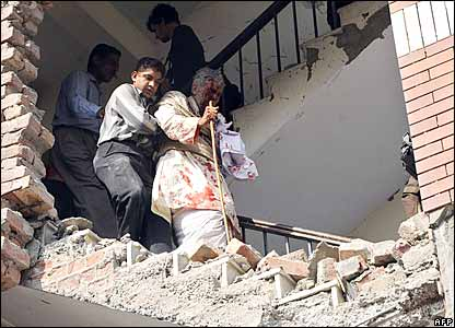 A Pakistani man helps a bomb blast victim to descend a stairway in a destroyed building of the Federal Investigation Agency