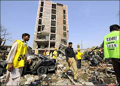 Pakistani rescue workers and police officials examine a bomb blast site in front of a destroyed building of the Federal Investigation Agency