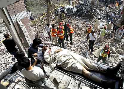Pakistani volunteers remove an injured man from the site of a bomb explosion at the office of the Federal Investigation Agency in Lahore,