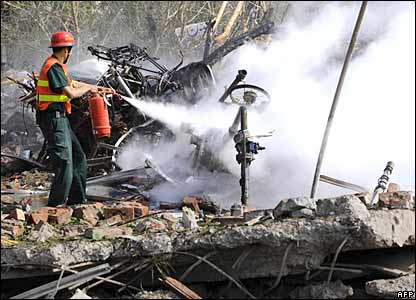 Pakistani rescuer uses a fire extinguisher at the bomb blast site in front of the badly damaged building of the Federal Investigation Agency