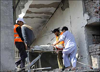 Pakistani rescue workers remove a bomb blast victim from the badly damaged building of the Federal Investigation Agency
