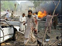 An injured man walks through the site of a suicide bombing at the office of the Federal Investigation Agency