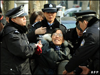 A demonstrator is detained by police outside the 13th Shanghai Municipal People Congress in Shanghai (24 January 2008)