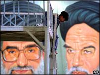 Un ni�o juega frente a un afiche del ayatol� Jomeini y el ayatol� Jamenei.
