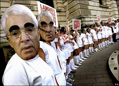 Conservative supporters wearing masks of UK Chancellor Alistair Darling