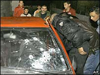 Palestinians gather round a car with bullet holes in the front windshield after four Palestinian militants were killed by Israeli troops in the West Bank town of Bethlehem