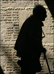 A man walks next to a wall with the names of fallen soldiers in Jerusalem