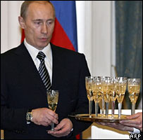 Former Russian President Vladimir Putin holds a glass of Champagne