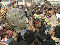 Iraqis celebrate with destroyed bust of Saddam Hussein, 26 December 2003