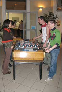 Kia and Anthony (foreground) play table football with friends