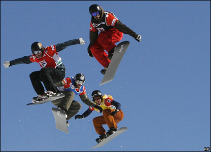Damon Hayler of Australia, Pierre Vaultier of France, Paul-Henri Delerue of France, and Simon Bonenfant of Canada fly through the air during the boarder cross event at the FIS Snowboard World Cup in Chiesa Valmalenco, Italy.