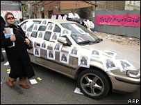 A woman walks past electoral leaflets on a car in Tehran on 13 March 2008