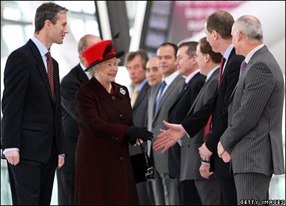 Queen shakes hands with people