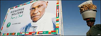A woman stands by a bill board of Senegal's President Abdoulaye Wade welcoming delegates to the OIC summit
