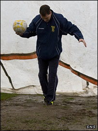 Referee Dougie McDonald inspects the un-playable pitch