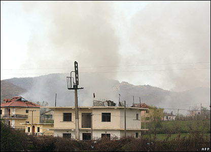 Smoke rising behind damaged buildings
