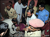 Pakistani guards carry out an injured foreigner after a bomb blast in Islamabad, 15 March 2008