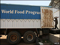 A worker loads a bag of food onto a WFP truck in Fasher, north Darfur
