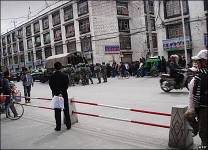 People watch Chinese military trucks in Lhasa, 16 March 2008