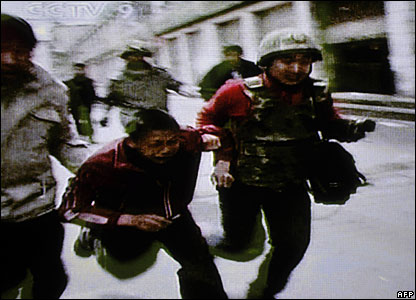 Grab from Chinese state television CCTV shows a boy being forced along a street in Lhasa, 16 March 2008
