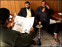 Iraqi men enjoying a hookah pipe and reading a newspaper